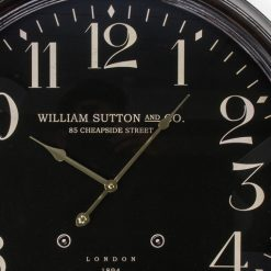 Close up showing brass style hands on black clock face