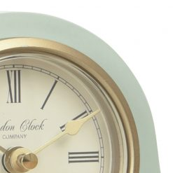 Close up of green mantle clock with gold trim