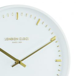 Close up of white art wall clock with gold finishings