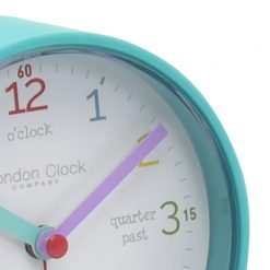 Close up of aqua coloured alarm clock with helpful time phrases