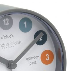 Close up view of grey alarm clock with time words on front