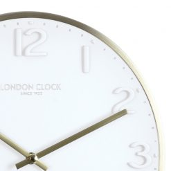 Close-up of round white Elvie wall clock with gold color hands