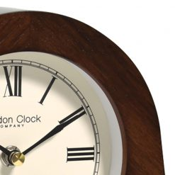 Close up of wooden silent mantle clock with black hands
