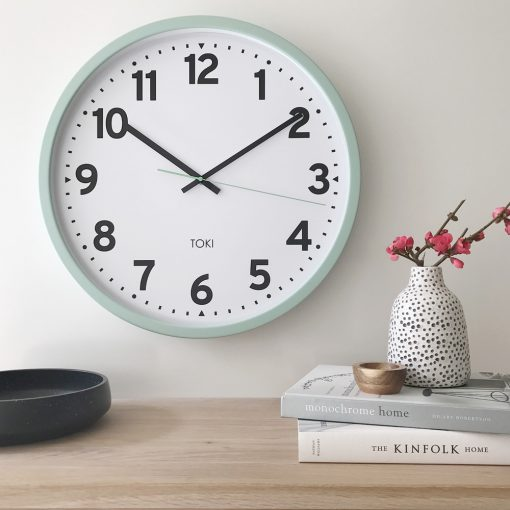 Lifestyle photo of 50cm wall clock with white face and duck egg colour outer case