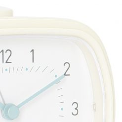 Close-up photo of cream colour silent sweep alarm clock with white face