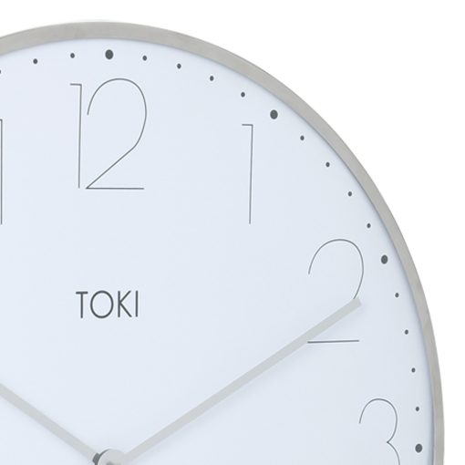 Close-up photo of large chrome silent sweep wall clock with white face
