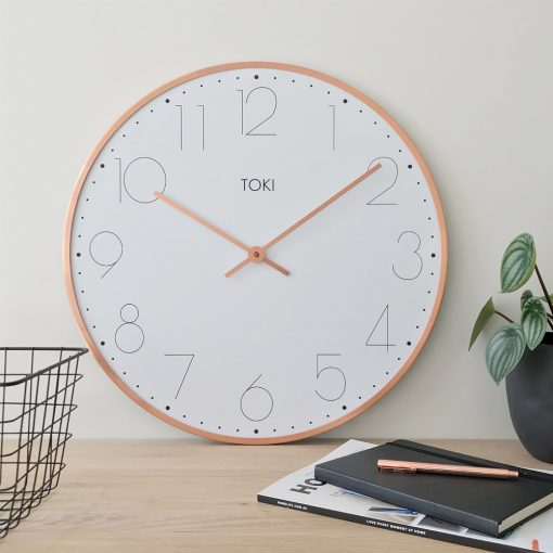 Lifestyle photo of 50cm silent sweep wall clock with white face and rose gold outer case