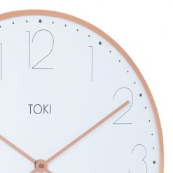 Close up image of large, silent sweep wall clock with rose gold case and white face