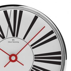Close-up image of contemporary chrome steel wall clock with large black numerals and red hands