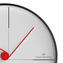 Close up image of white contemporary wall clock with red hands and black steel outercase