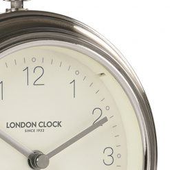 Close up photo of gun metal coloured alarm clock with white face