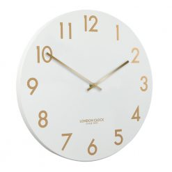 Angled view of large chalk white metal wall clock with gold hands