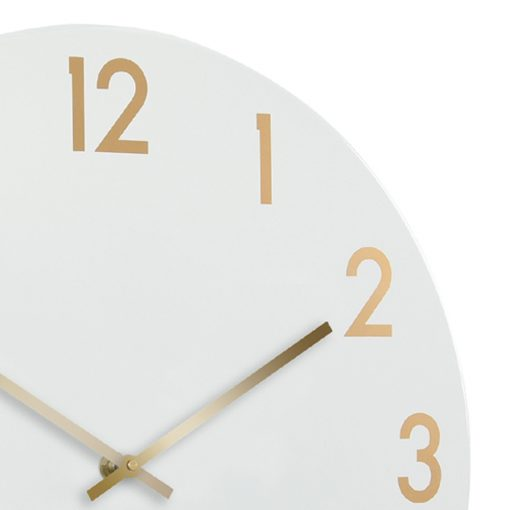 Close up photo of large chalk white metal wall clock with gold numbers