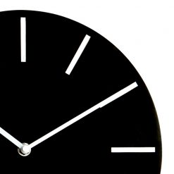 Close up photo of modern wall clock with black face and white markers