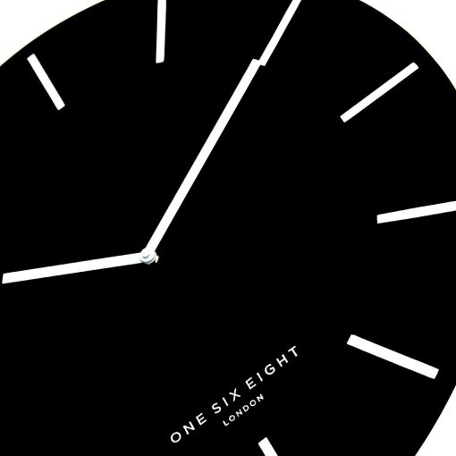 Close up photo of large silent wall clock with black face and white markers