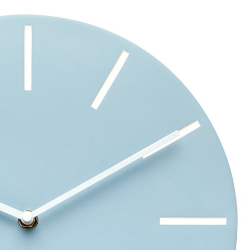 Close up photo of modern blue wall clock with white hands and markers
