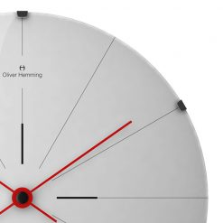 Close-up image of stainless steel wall clock with black markers and red hands
