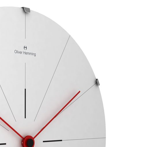 Side view photo of stainless steel wall clock with red hands and thin markers