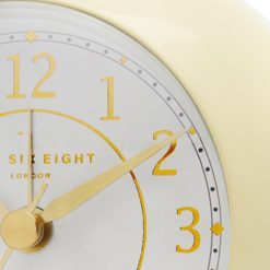Close up image of round cream coloured alarm clock with silent tick