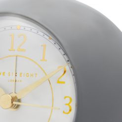 Close-up photo of grey silent alarm clock with gold hands