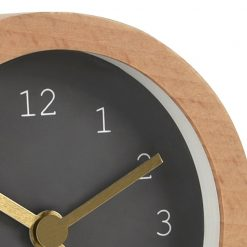 Close up photo of wood coloured alarm clock with grey face