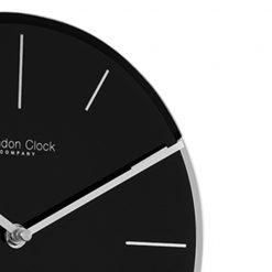 Close up image of black glass pendulum wall clock and metal hands