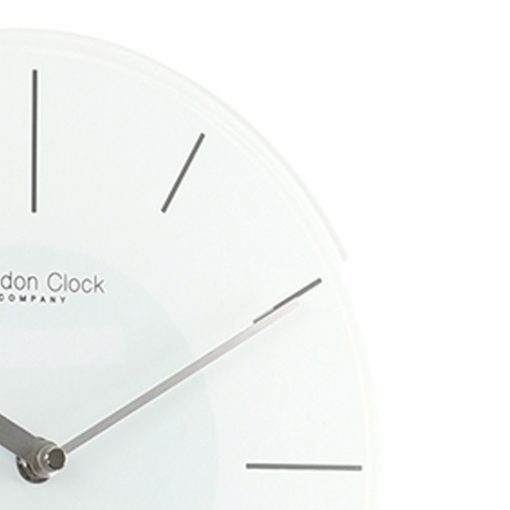 Side view close up photo of white glass pendulum wall clock and grey markers