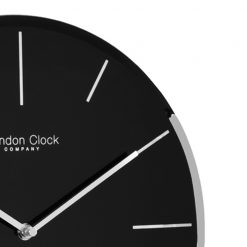 Close up photo of black glass wall clock with silver hands