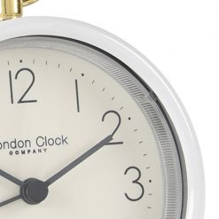 Close up image of white alarm clock with grey hands and gold hoop