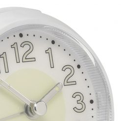 Close up image white alarm clock with illuminating dark numbers