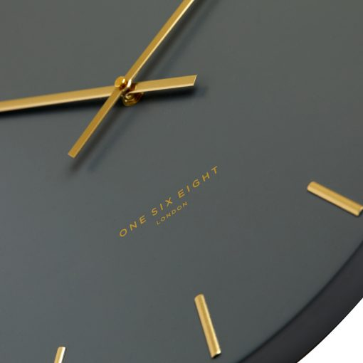 Close up photo of large charcoal coloured silent wall clock with gold markers