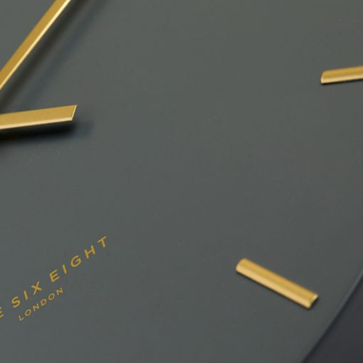 Close up photo of charcoal coloured silent wall clock with gold hands