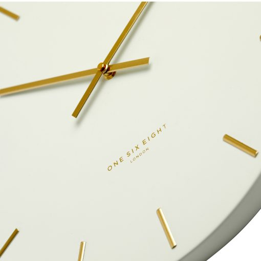 Close-up image of large white silent wall clock gold hands