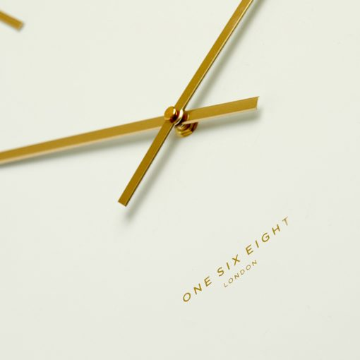 Close-up view white silent wall clock with gold hands