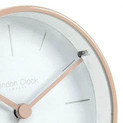Close up image of alarm clock with blush coloured outer case and hands