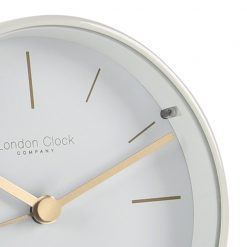 Close up photo of white alarm clock with gold hands and markers