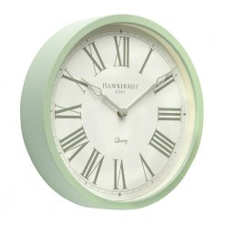 Angled photo of sage green wall clock with roman numerals and white face