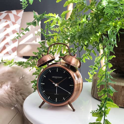 Copper alarm clock shown with a black face witting on a white table net to a leather sofa