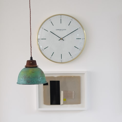 Wall scene showing a sleek modern wall clock on a wall with a teal pendant light hanging in the foreground